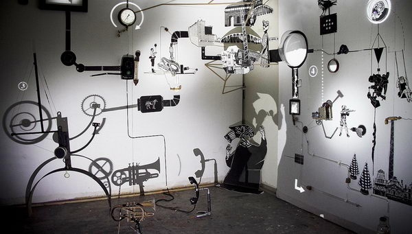 Rube Goldberg Style Installation Art, This is an art installation that combines Rube Goldberg logic with light, shadows, wooden shapes, found objects, and full motion video.