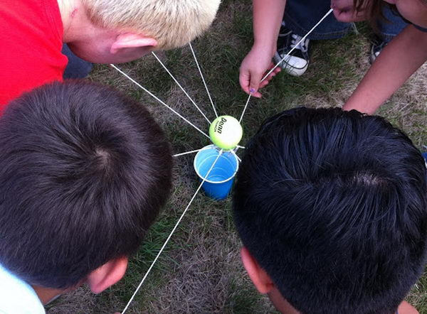 Tennis Ball Transfer Team Building Activities. This requires a large metal washer and a tennis ball for each group. The groups have to hold the strings and balance a tennis ball on the washer while walking and moving towards a plastic cup a distance away. Once the team successfully reaches the cup without dropping the ball, they have to work together to figure out how to get the ball into the cup without touching either one.