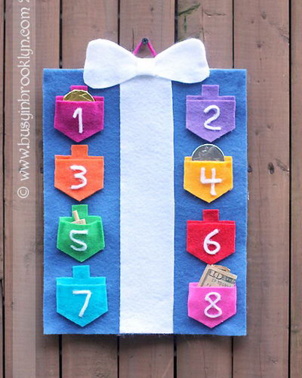 A countdown-to-Hanukkah calendar with draidel pockets for each night. The pockets are perfect little holders for Chanukah chocolate coins, the real (green) stuff, draidels and little gifts.