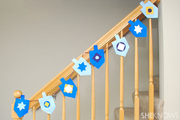 Decorate the railing and mantel with the felt dreidel banner.