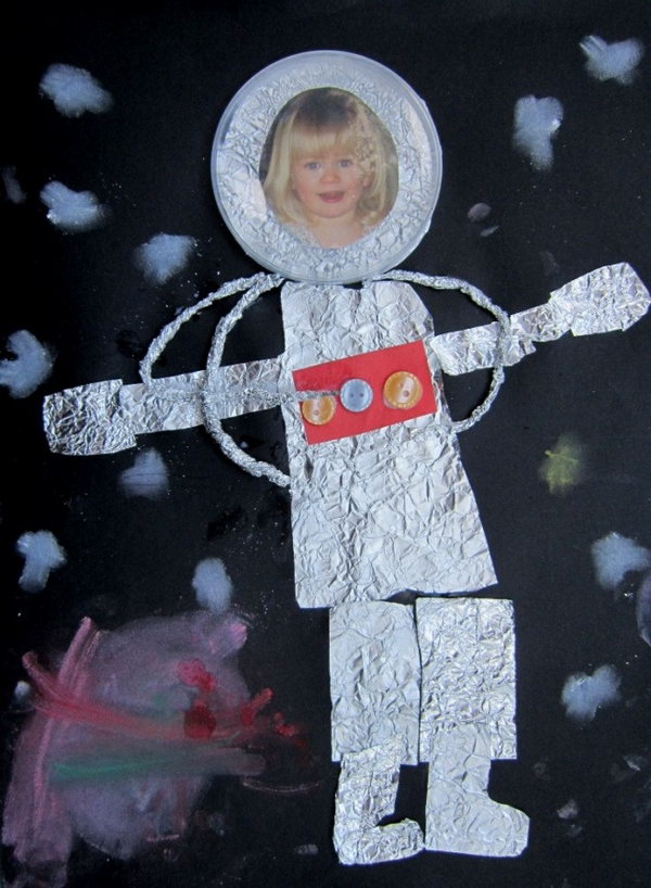 Astronaut craft made from Kitchen foil, buttons, photo, clear lid, coloured card and soft pastel.