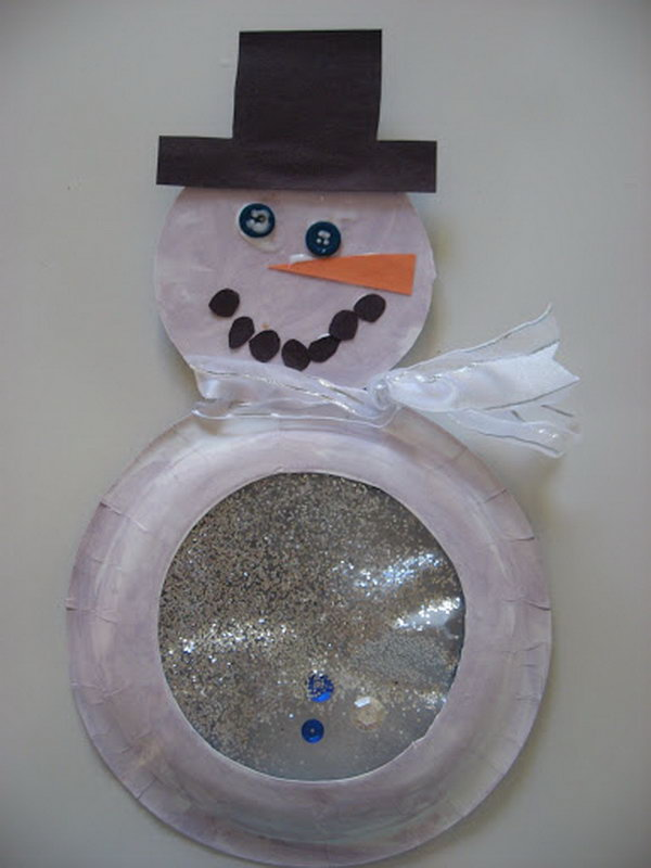 Snowglobe snowman made with paper plate, buttons, sparkles and ribbon.
