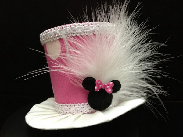 This adorable pink minnie mouse mini top hat is the perfect choice for your lovely daughter. White feathers are attached to the side along with cute Minnie Mouse head with pink polka dot bow to complete this adorable look!