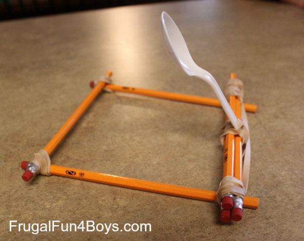 Pencil Catapult. This catapult is built out of unsharpened pencils, rubber bands, and a plastic spoon. The process of making is so easy, your kids can make it by themselves just according to this picture.