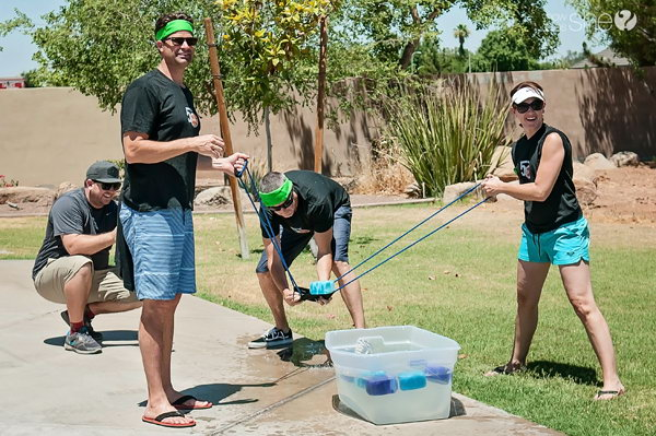 Sponge Launch. Three team members use the water balloon launch to launch sponges filled with water to their team mates. Teammates catch the sponges and wring the sponge out in the bucket. Once the bucket is full, you win the game.