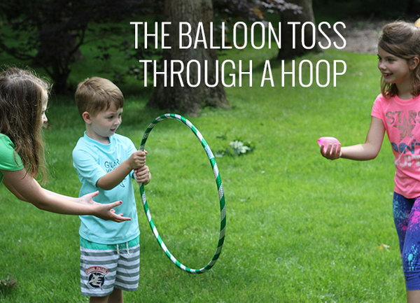 Balloon Toss through a Hoop. Ask one kid to hold the hula-hoop and the other kid try to toss the water balloon through the hoop. It's challenging yet interesting.